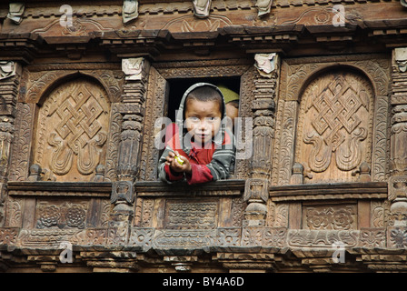 A Tamang boy watches from a window in an elaborately carved wooden house, Gatlang, Tamang Heritage trek, Nepal - Stock Photo
