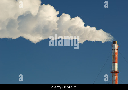 Smoke, gas and steam billows from a smokestack against a blue sky. - Stock Photo
