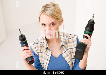 Home improvement - woman with battery cordless screwdriver - Stock Photo