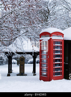 Red traditional telephone box with snow on a English village green - Stock Photo