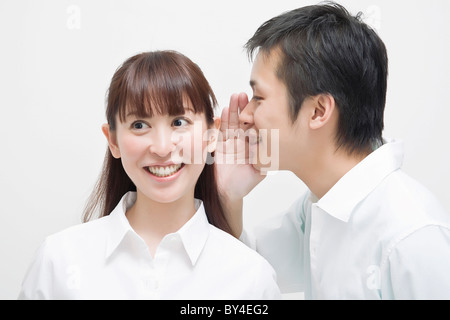 Man whispering to woman - Stock Photo