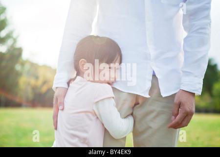 Girl hugging father's leg - Stock Photo
