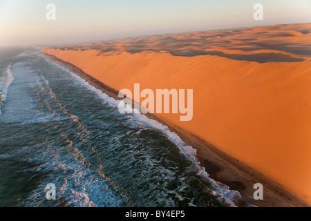 Aerial view over sand dunes & sea, Namib Desert, Namibia - Stock Photo