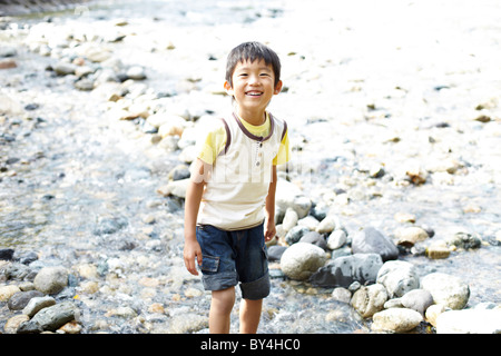 Cheerful Boy Playing in Stream - Stock Photo