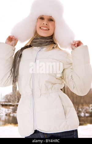 Portrait of young woman wearing white fur cap and warm jacket in winter - Stock Photo