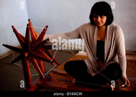 A girl using spinning wheel to make thread - Stock Photo