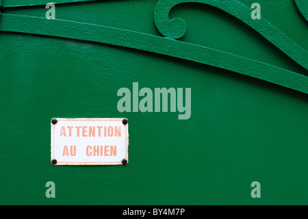 An 'Attention Au Chien' sign on a green gate in a French village. - Stock Photo