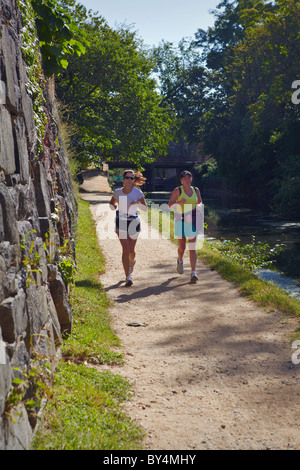 Two women jogging on the towpath of the C&O Canal in Georgetown, Washington, DC. - Stock Photo