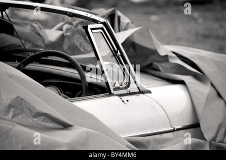 A covered up white convertible classic MG car ready to be fixed, done up and driven - Stock Photo