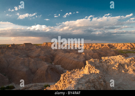 A storm rolls in over the plateaus of Badlands National Park at dusk - Stock Photo