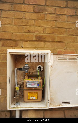 Mains gas meter mounted inside a cabinet built into the outside brick wall of a new build house - UK - Stock Photo