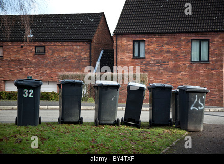 A row of grey plastic wheelie bins awaiting emptying by bin men in a street in Redditch, Worcestershire, UK - Stock Photo