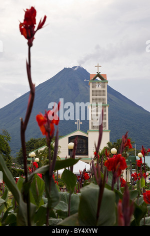Red Canna Lilies and church in La Fortuna de San Carlos with the Arenal Volcano in the background, Alajuela, Costa - Stock Photo