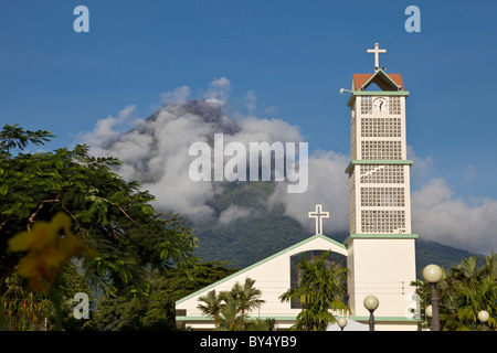 Clouds obscure the looming Arenal Volcano behind the central church church in La Fortuna de San Carlos, Alajuela, - Stock Photo