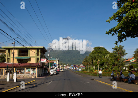 Morning clouds obscure the upper cone of the looming Arenal Volcano in La Fortuna de San Carlos, Alajuela, Costa - Stock Photo