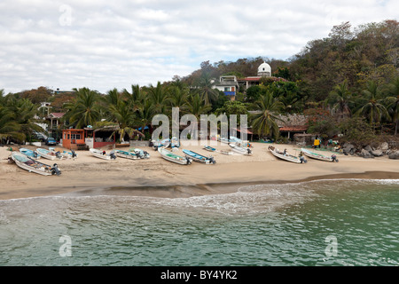 azure water laps golden sand with fishing boats drawn up on palm fringed beach at evening Puerto Angel Oaxaca State - Stock Photo