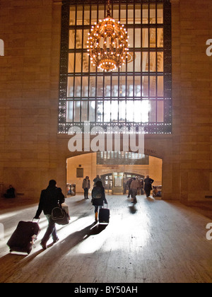 In afternoon sun, travelers with luggage head for the 42nd Street exit of Grand Central Station in midtown Manhattan, - Stock Photo