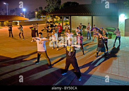 An Asian American college student conducts an informal night hip hop dancing class outdoors on campus in California. - Stock Photo