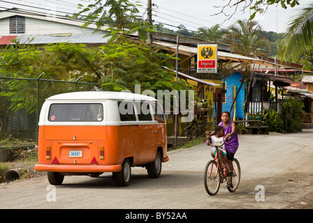 Two kids riding a bike on the street with an orange VW bus Puerto Viejo, Costa Rica. - Stock Photo