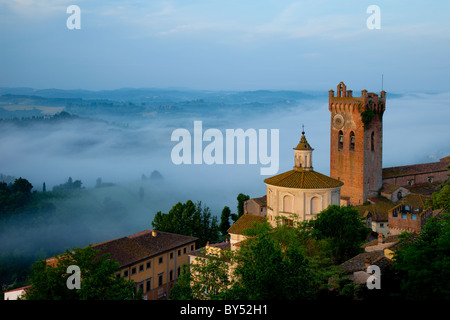 Pre-dawn mist laying in the valley below the duomo and medieval town of San Miniato, Tuscany Italy - Stock Photo