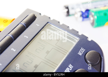 Accumulator battery charger with batteries on white background - Stock Photo