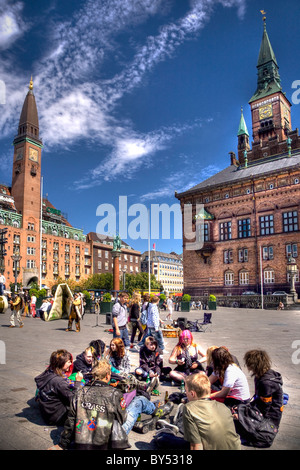 Group of young people sitting at Copenhagen town hall square - Stock Photo