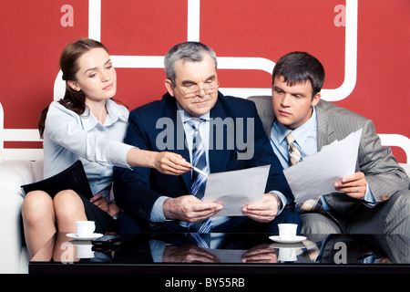 Serious men looking with interest into business plan in chief's hands at which pretty woman pointing while sitting - Stock Photo
