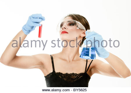 Young woman holding test tubes in hands during scientific experiment - Stock Photo