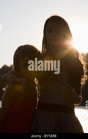 A girl with her arm around her little sister, portrait - Stock Photo