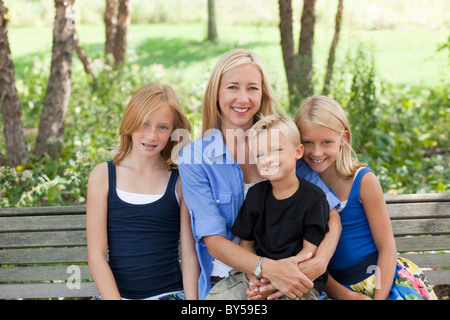 Mom and three kids on a bench - Stock Photo