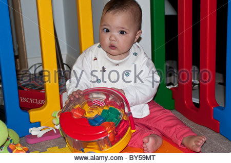 Ten month old baby girl playing with colourful toy - Stock Photo