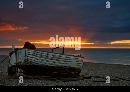 Sunrise Dunwich Beach and traditional Suffolk Fishing boat on shore - Stock Photo