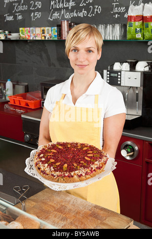 A sales clerk holding a fruit and nut tart - Stock Photo