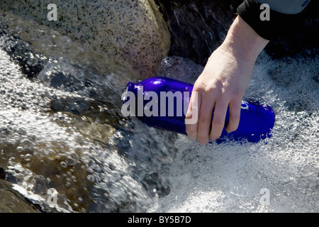 Detail of a person filling a drink bottle in a river - Stock Photo