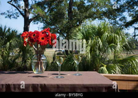 Two glasses of white wine and a vase of Gerbera daisies on a table, outdoors - Stock Photo