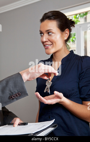 A real estate agent giving a woman the keys to her new home - Stock Photo