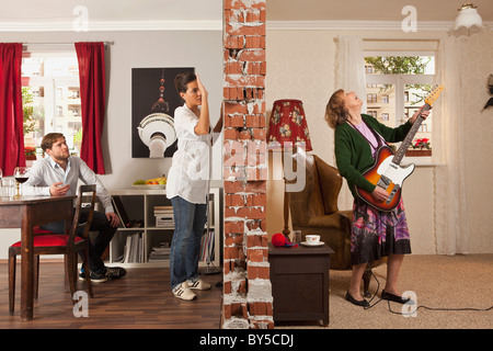 A split screen showing an angry woman pounding on the wall to her neighbor - Stock Photo
