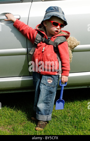 A young boy waiting beside a car, ready to go. - Stock Photo