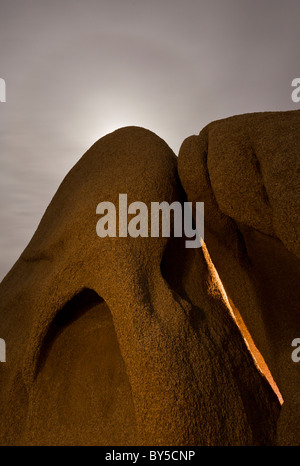 Moon shining from behind large granite boulders at night in Joshua Tree National Park, Mojave Desert, California, - Stock Photo