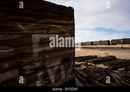 Abandoned depot with train in the distance along Highway 62 in the now ghost town of Rice, California, USA. - Stock Photo