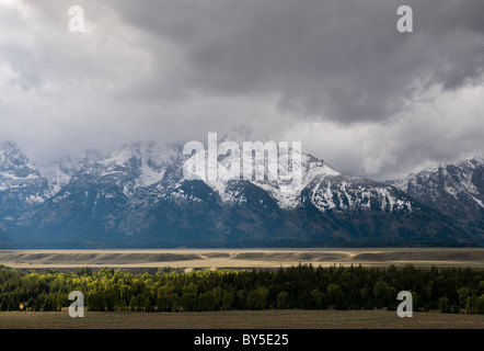 sunlight breaking through clouds on the Tetons - Stock Photo