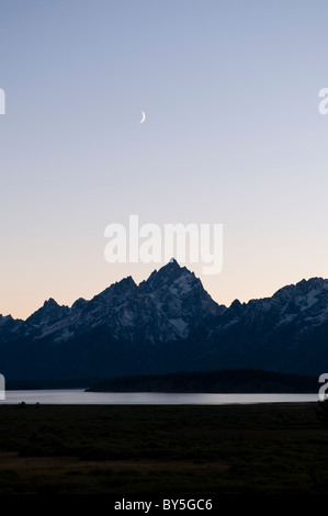 Moon over the Grand Teton at dusk from Jackson Lake Lodge - Stock Photo