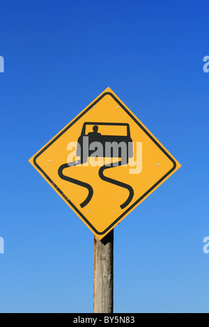 slippery road sign with car and skid marks in black on yellow with blue sky background - Stock Photo