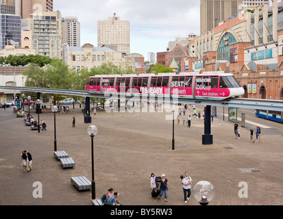 Sydney Monorail running on an overhead track between Darling Harbour and Paddy's Market in Sydney CBD as pedestrians - Stock Photo