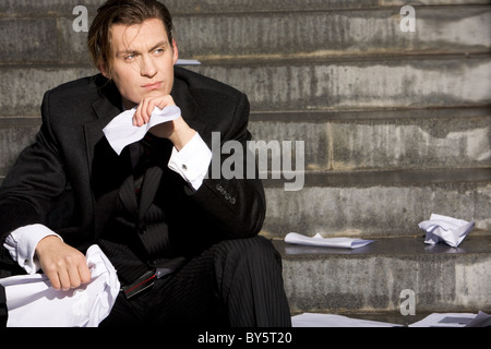 Portrait of thoughtful business man touching his chin and looking aside - Stock Photo