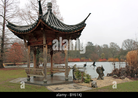 Japanese Pagoda and sculptures at the frozen lake in Seven Acres, RHS Garden Wisley, Surrey, England, Great Britain, - Stock Photo