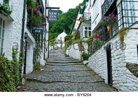 Clovelly's steep cobbled street leads down to a picturesque harbour. Clovelly Court, Bideford, Devon, UK - Stock Photo