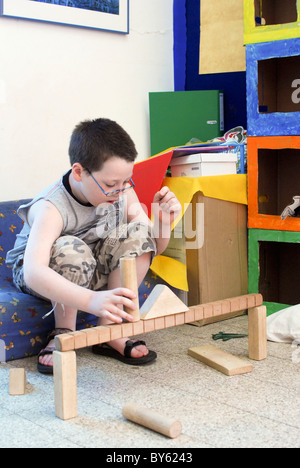Young boy of 8 building with wooden building blocks in a playroom - Stock Photo