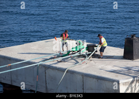 Harbour workers casting off the mooring hawser of the passenger ship Ventura. Ajaccio Corsica - Stock Photo