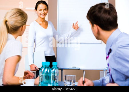 Portrait of business woman demonstrating something on the whiteboard at seminar - Stock Photo